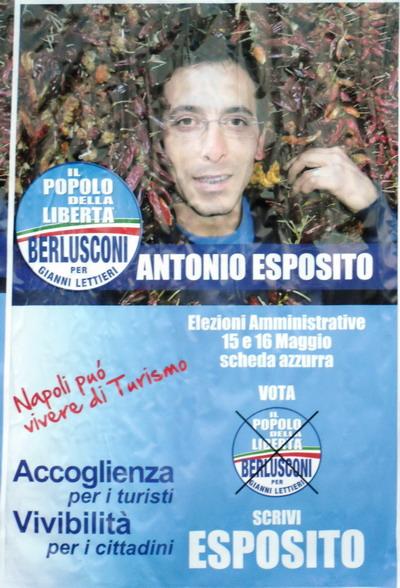 Il candidato Antonio Esposito, la cui faccia emerge da una fitta siepe di peperoncini rossi