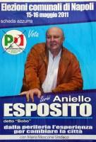 il candidato esposito, del pd, in una strana postura obliqua, si regge con una mano al bordo della scritta